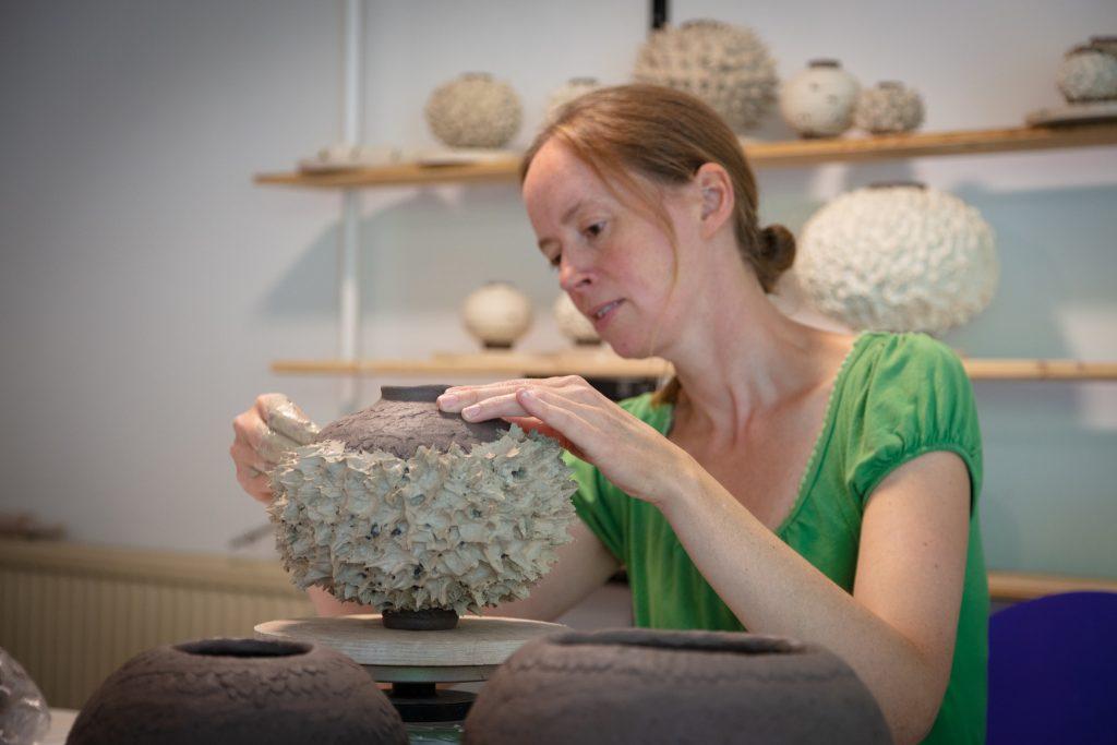 Maja Frendrup arbejder på en keramikkrukke